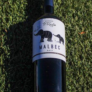 Red wine bottle on grass.