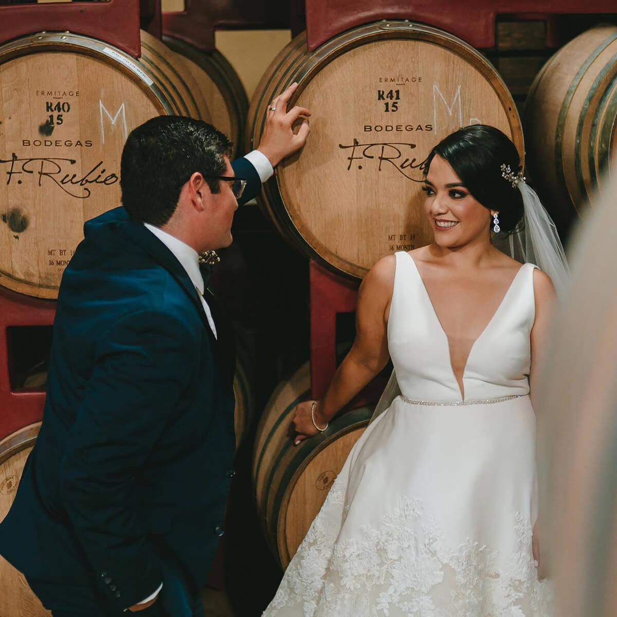 Pareja de recién casados frente a barricas de vino.
