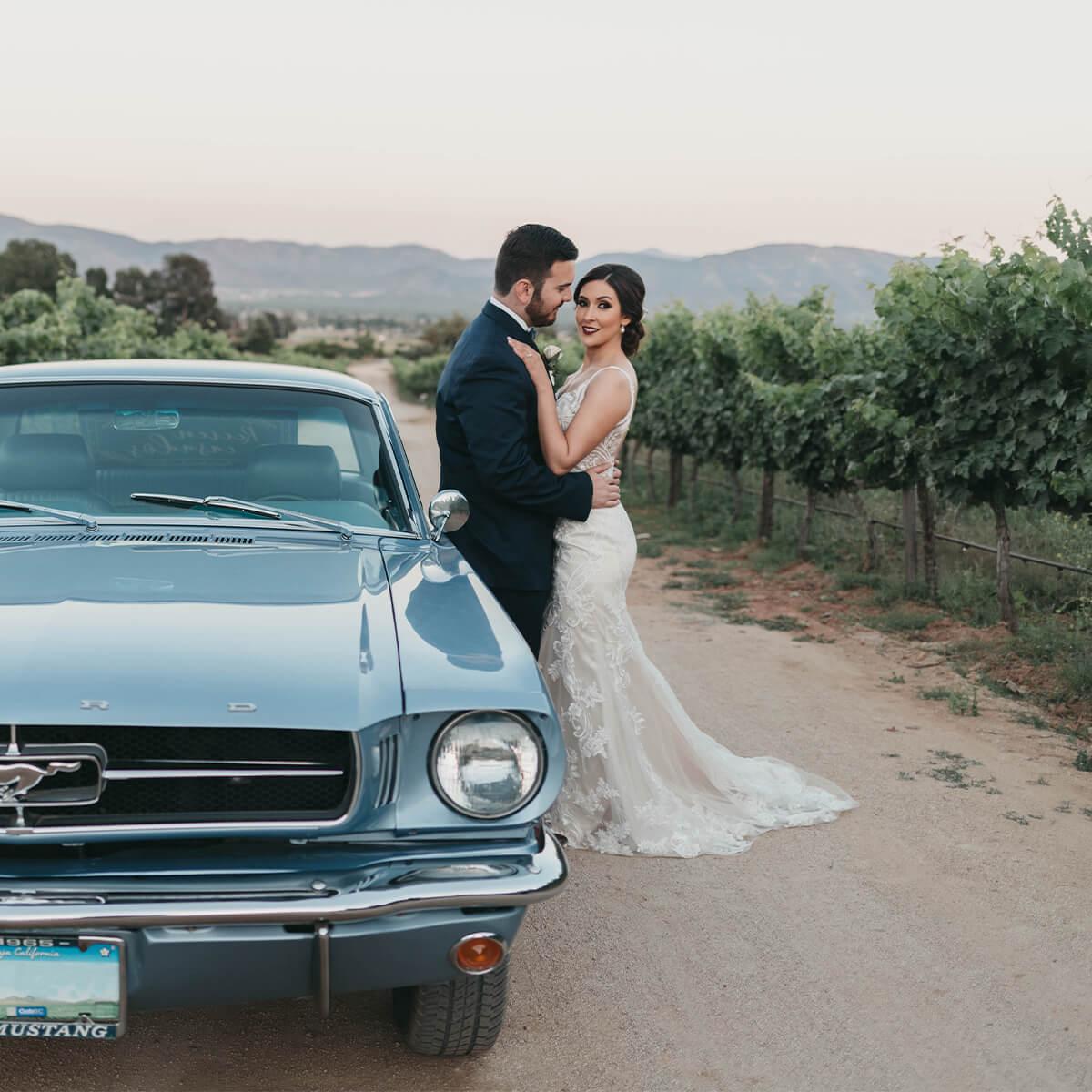Pareja de recién casados frente a un auto en los viñedos de Bodegas F. Rubio.