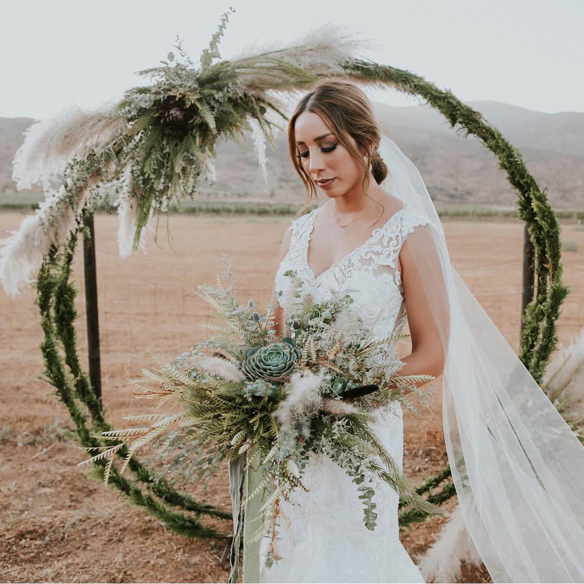 Novio sosteniendo ramo de boda en Valle de Guadalupe.