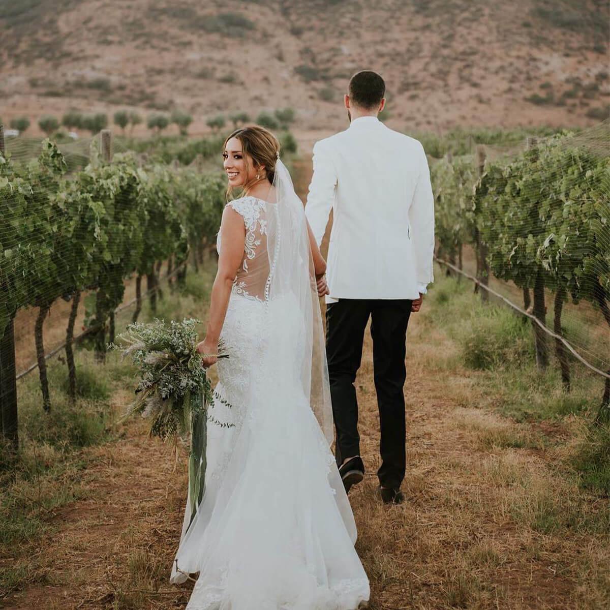 Pareja de recién casados caminando en un viñedo.