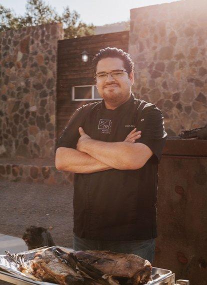 Chef Alex Rubio parado frente a un asado.