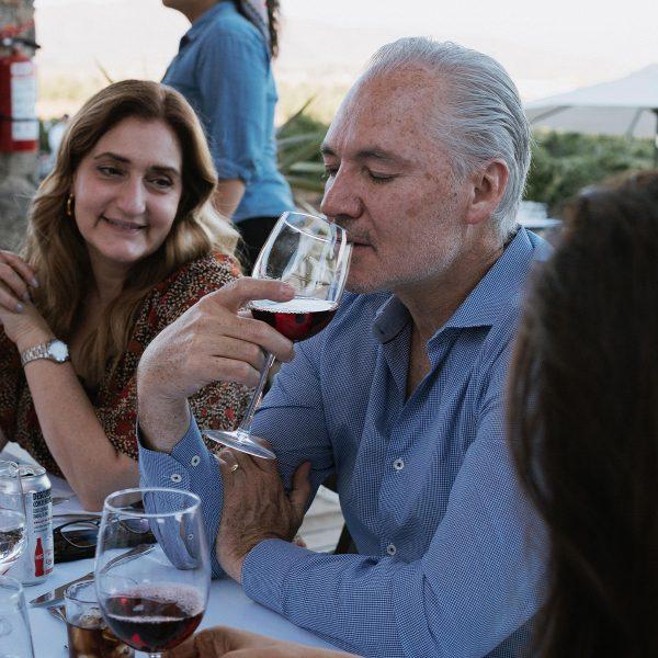 Hombre junto a su familia disfrutando de una copa de vino tinto.