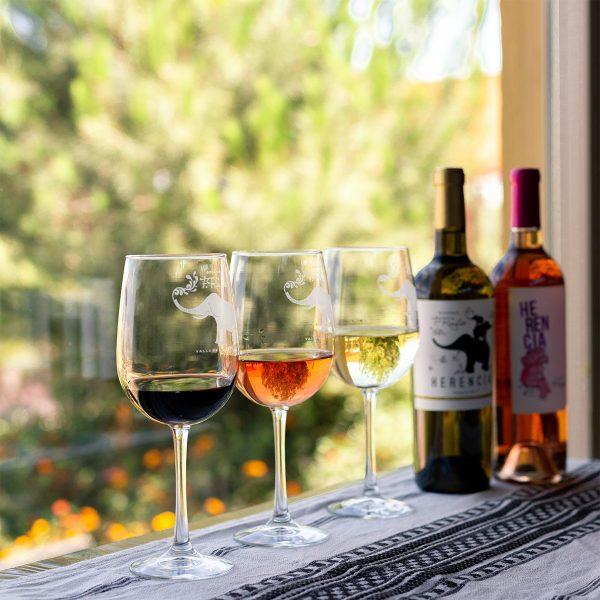 Copas de vino tinto, blanco y rosado junto a botellas de vino.