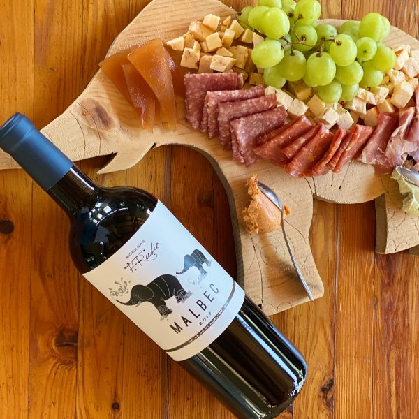 Botella de vino Malbec junto a aperitivos de Parcela 70.