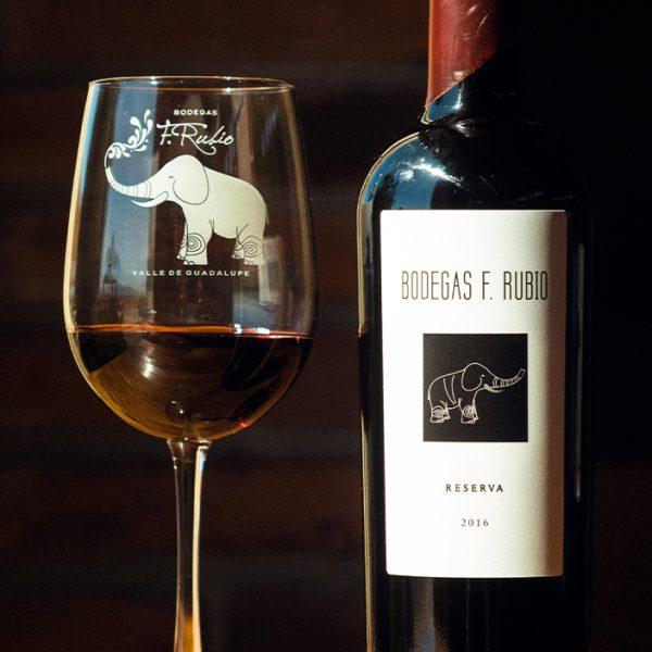 Botella de vino Reserva junto a copa de vino.