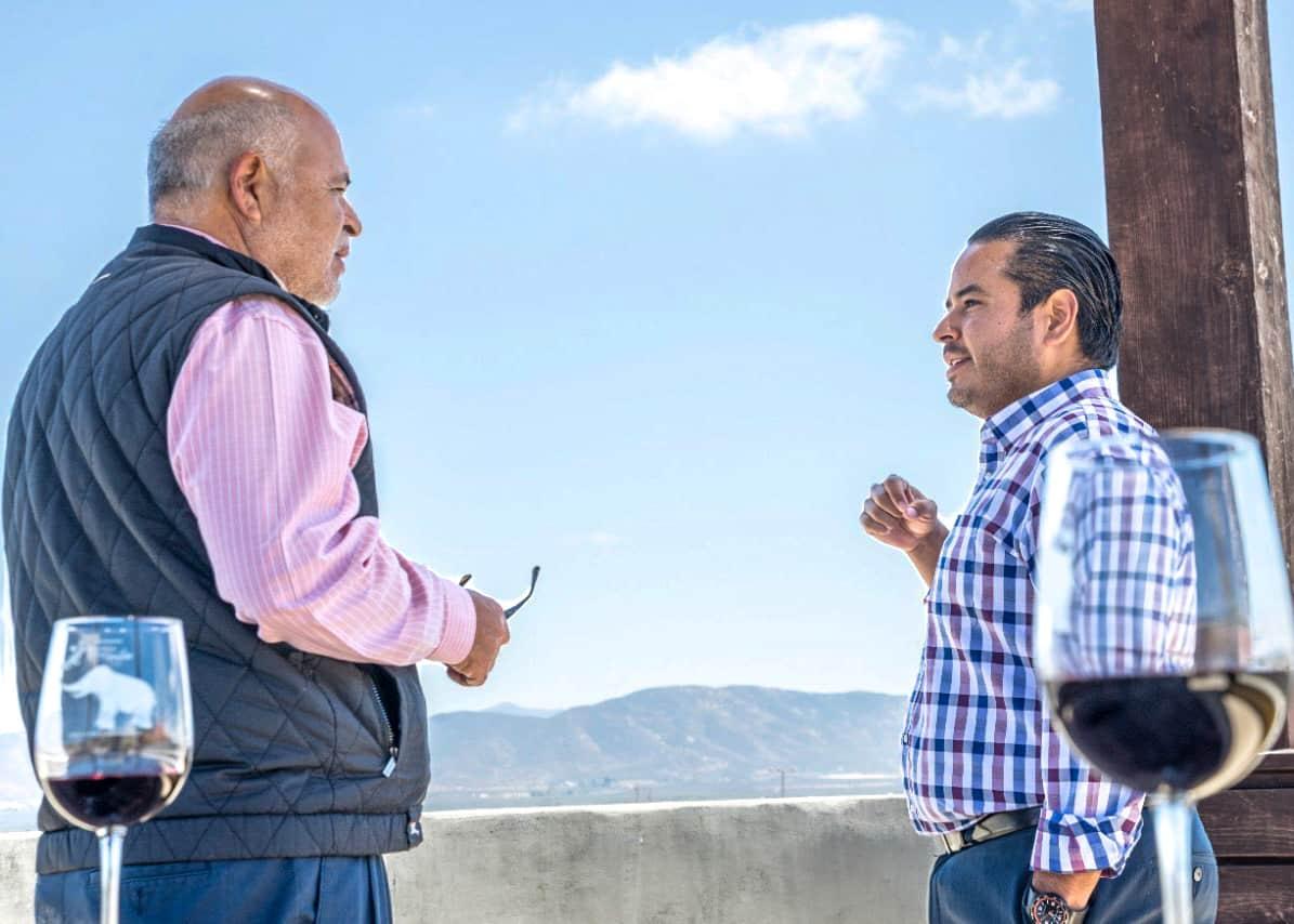 Padre e hijo hablando frente a Valle de Guadalupe.
