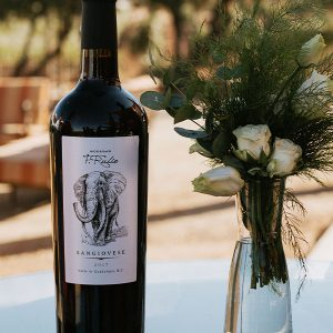 Bottle of Sangiovese wine with a flower arrangement.