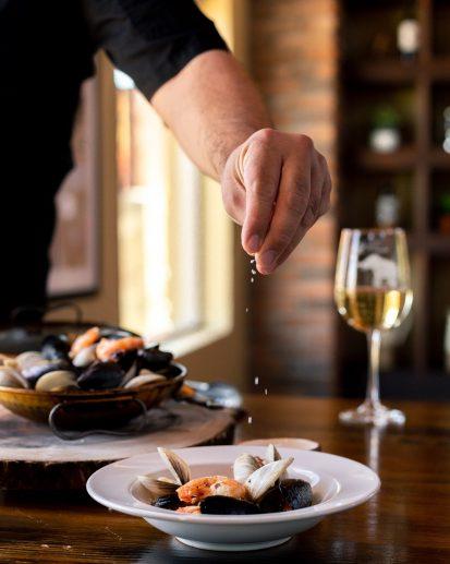 Chef esparciendo condimento a platillo de mariscos.